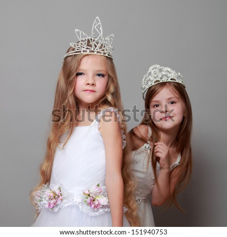Two European girls in white dresses and a crown on a gray background - stock photo