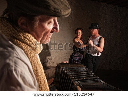 Two European tango dancers turning as squeezebox performer plays - stock photo