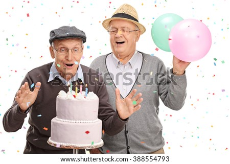 Two excited senior gentlemen blowing candles on a birthday cake isolated on white background - stock photo