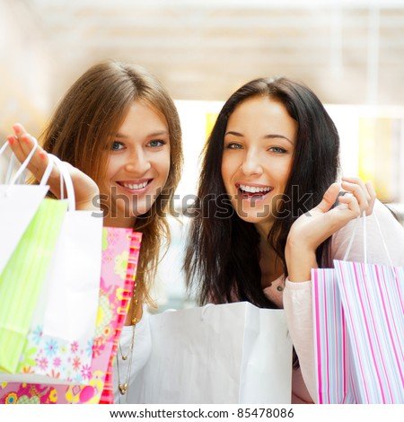 Two excited shopping woman together inside shopping mall laughing and gossip. Horizontal Shot - stock photo
