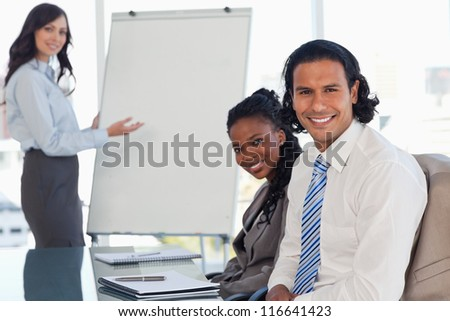 Two executives sitting at a desk in a meeting room during a presentation - stock photo