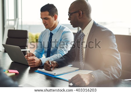 Two experienced business executives in a meeting seated at a table discussing paperwork and information on a laptop computer, one Hispanic, one African American - stock photo