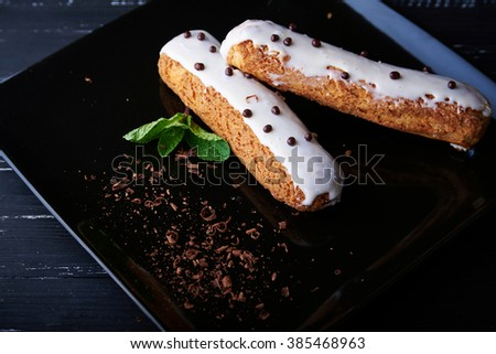 Two exquisite cream dessert eclair with fresh mint leaves on a black plate. Shallow depth of field - stock photo