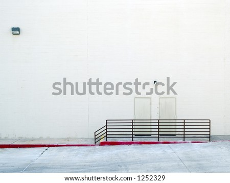 Two exterior doors of an anonymous, bland warehouse building. - stock photo