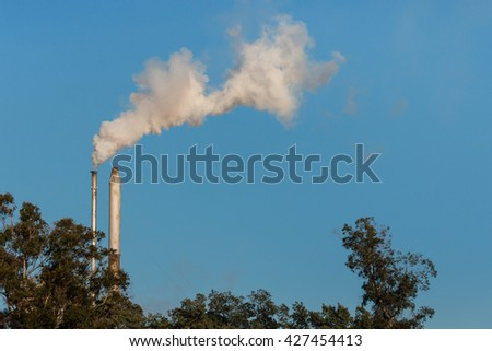 two factory smokestacks with copy space - stock photo