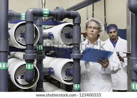 Two factory workers inspecting at bottling plant - stock photo
