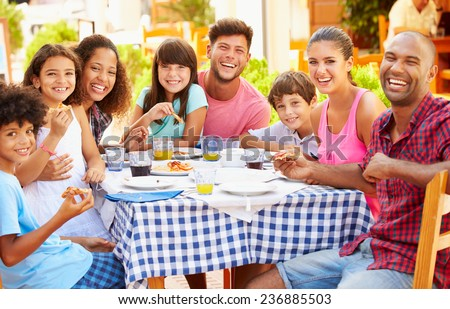 Two Families Eating Meal At Outdoor Restaurant Together - stock photo