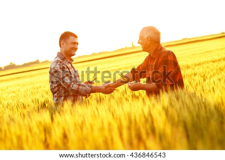 Two farmer standing in a wheat field and shake hands on sunset. - stock photo