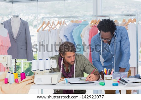 Two fashion designers working together on a desk - stock photo