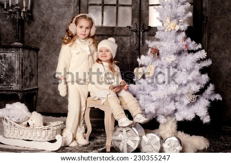 Two fashion girl in knitted clothes waiting for Christmas near eve and gift boxes - stock photo