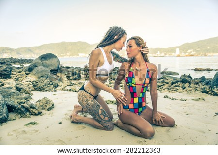 two fashion model posing on the beach in bikini. they almost kissing each other for fun. concept about fashion beauty, sex and people - stock photo