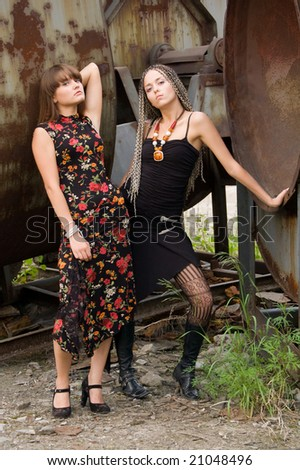 two fashionable girls on the dirty industrial place alongside of constructions - stock photo