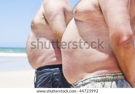 Two fat men showing their bellies on the beach - stock photo