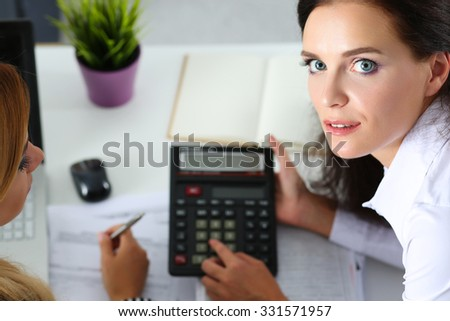 Two female accountants counting on calculator income for tax form completion closeup. Internal Revenue Service inspector checking financial document. Planning budget, audit, insurance concept - stock photo