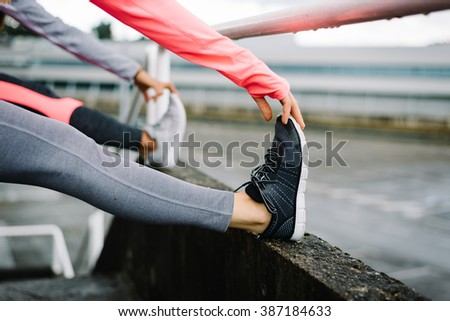 Two female athletes stretching legs and exercising. Sporty fitness women doing warm up workout before training. - stock photo