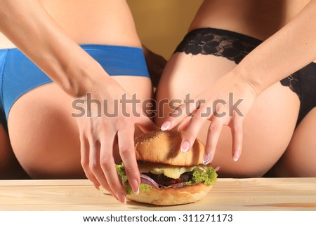 Two female bottoms of young ladies in blue and black lace panties holding one big fresh tasty burger of green lettuce meat cutlet cheese onion and white bread bun with sesame seeds, horizontal picture - stock photo
