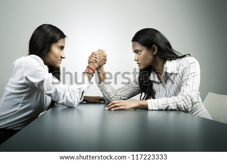 Two female business colleague's having an arm wrestle competition. Conceptual business image about power and control. - stock photo
