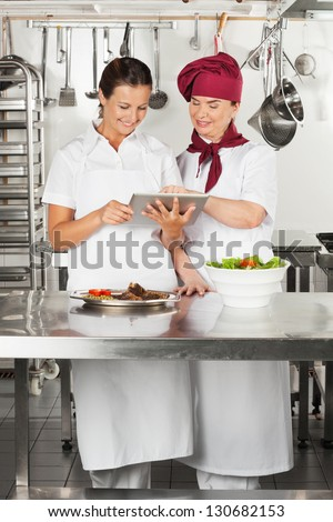 Two female chefs looking for recipe on a digital tablet while cooking at kitchen - stock photo