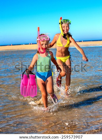 Two female children playing on beach.  Blue sky. - stock photo