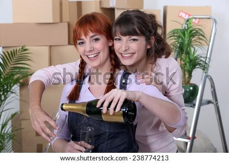 Two female flat-mates celebrating move - stock photo