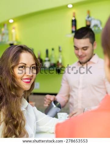 Two female friends chatting and drinking wine in the bar - stock photo