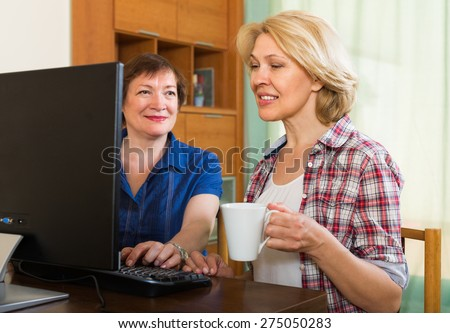 Two female friends drinking tea and browsing web - stock photo