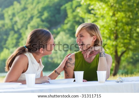 two female friends having picnic outdoors and laughing - stock photo
