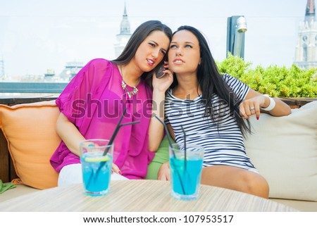 Two female friends in cafe - stock photo