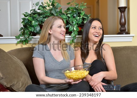 Two female friends laugh as they watch off frame television in living room of home - one Caucasian and one biracial (white and Asian) - bowl of popcorn in lap - stock photo