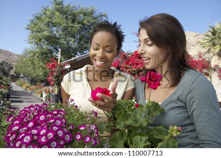 Two female friends looking at flowers in botanical garden - stock photo