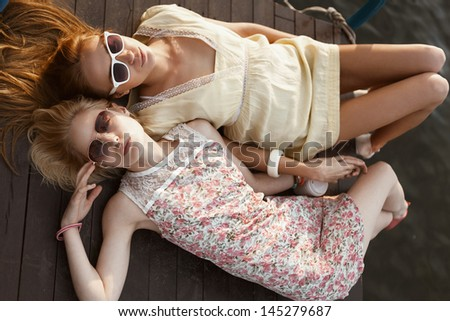 Two Female Friends lying near the water. Outdoors, Lifestyle - stock photo