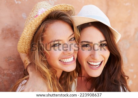 Two Female Friends On Holiday Together Posing By Wall - stock photo