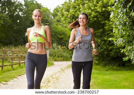 Two Female Friends On Run In Countryside Together - stock photo