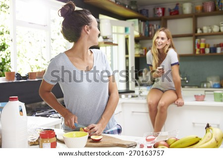 Two Female Friends Preparing Breakfast At Home Together - stock photo