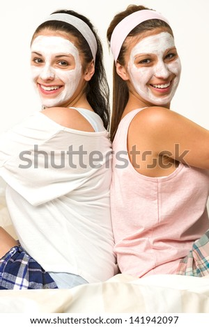 Two female friends sitting back-to-back with white facial mask - stock photo
