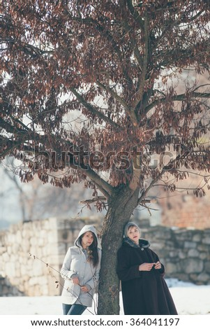 Two female friends standing beside tree   - stock photo