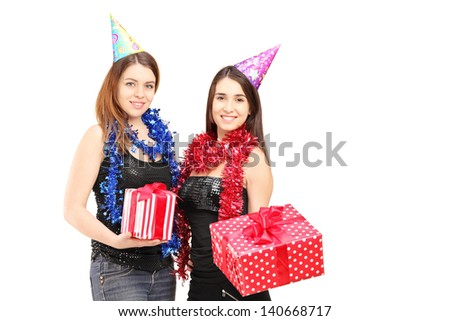 Two female friends standing close together and holding gifts at party isolated on white background - stock photo