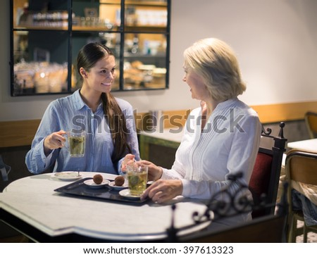 Two female friends talking at cafe table and smiling - stock photo