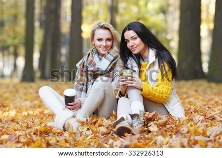 Two female friends with take away coffee in autumn park - stock photo