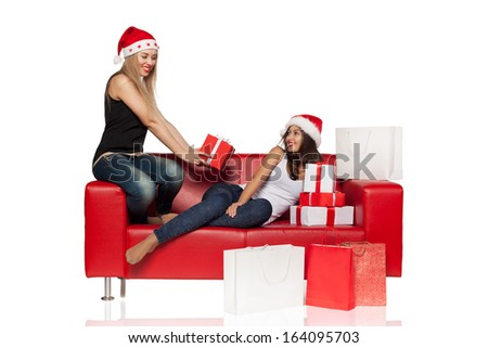 Two female girl friends  sitting on the red sofa, surrounded by shopping bags and gifts, isolated over white background - stock photo