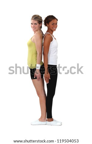 Two female gymnasts stood back to back - stock photo