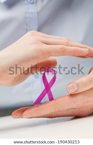 Two female hands gently holding and protecting a pink cancer awareness ribbon. - stock photo