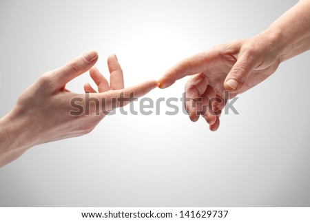 Two female hands of different ages gently touching with the index fingers. - stock photo
