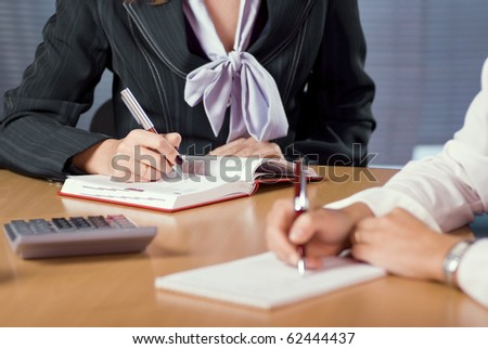 two female hands that taking notes at the meeting - stock photo