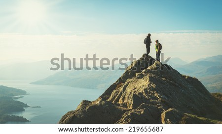 Two female hikers on top of the mountain enjoying valley view, Ben A'an, Loch Katrina, Highlands, Scotland, UK - stock photo