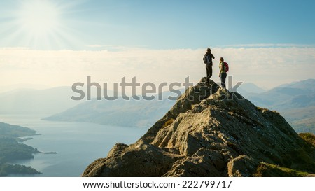 Two female hikers on top of the mountain enjoying valley view, Ben A'an, Loch Katrine, Highlands, Scotland, UK - stock photo