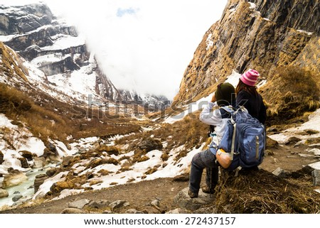 Two female hikers resting while enjoying the serene view of the snowy trek - stock photo