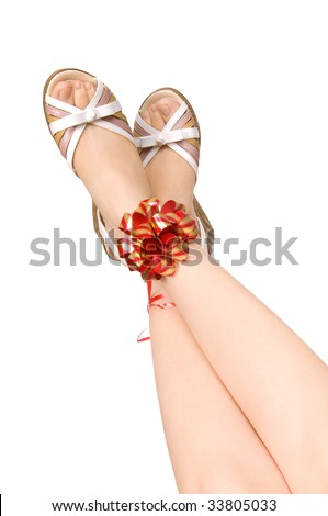 Two female legs in shoes tied up by a red tape with a bow, on a white background, isolated - stock photo