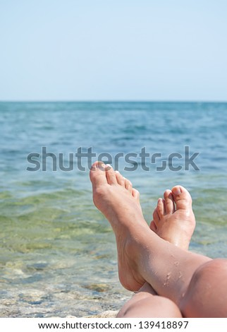 two female legs on beach over sea waves and blue sky - stock photo