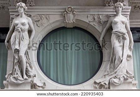 Two Female Neoclassic Marble Statues next to a Round Window - stock photo